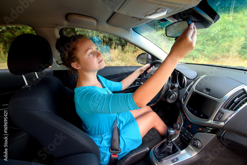 Side view of stylish girl in dress touching rear view mirror