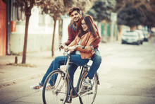 Young Couple Riding Bicycle At...