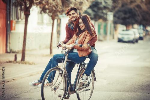 Zdjęcie XXL Potomstwo pary jeździecki bicykl przy ulicą na jesień dniu. Siedzą na rowerze i robią zabawie.
