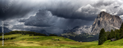 Photo sur Toile Tempete Storm over the mountains Dolomiti in the summer season with meadow in foreground