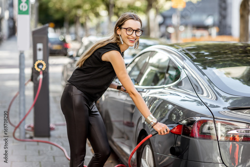 Fotografía  Young woman in black clothes putting connector into the electric car outdoors on