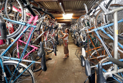A mechanic installs second-hand bicycles in the shop named