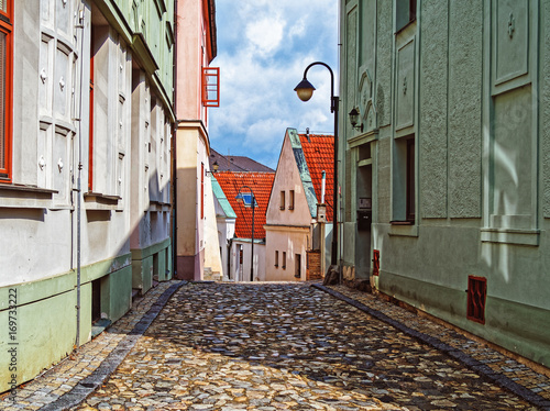 Fényképezés Narrow street covered with stone blocks in the town of Tábor, Czech Republic