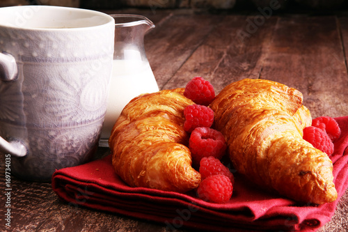 Photo Stands Coffee beans Coffee white cup, croissants on brown wooden background. Breakfast concept