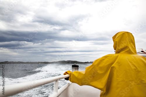 persona de espalda con un impermeable amarillo en un barco bajo la lluvia y un cielo gris con nubes
