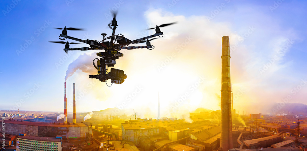 Fototapety, obrazy: Professional drone flying over factory at sunset