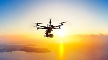Innovation Photography Concept. Silhouette Of The Professional Drone With Cinema Camera Hovering In The Summer Sunset. Heavy Lift Drone Photographing City At Sunset.