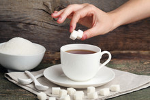 Female Hand Throwing Sugar Cubes In Cup Of Tea