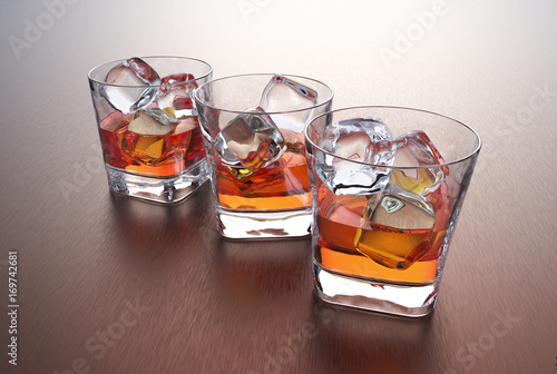 Photo  Three glasses of whiskey with ice cubes on a metal table.