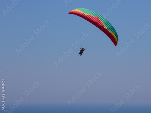 Foto op Canvas Luchtsport Flying tandem paragliders in the sky over the sea and near the mountains, beautiful sea view 02