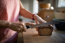 Senior Woman Cutting Bread Loaf In The Kitchen