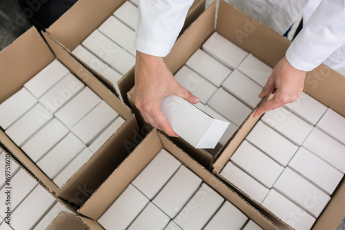 High-angle close-up view of the hands of a manufacturing worker putting packed p Wallpaper Mural
