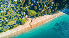 Aerial View On Small Suburb On A Sunny Ocean Beach. Coromandel Peninsula, New Zealand