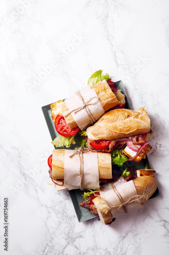 Staande foto Snack Fresh baguette sandwich bahn-mi styled. Bacon, roasted cheese, tomatoes and lettuce on metallic tray on white marble background. Vertical composition.