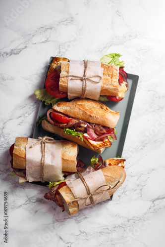 Staande foto Snack Fresh baguette sandwich bahn-mi styled. Bacon, roasted cheese, tomatoes and lettuce on metallic tray on white marble background.