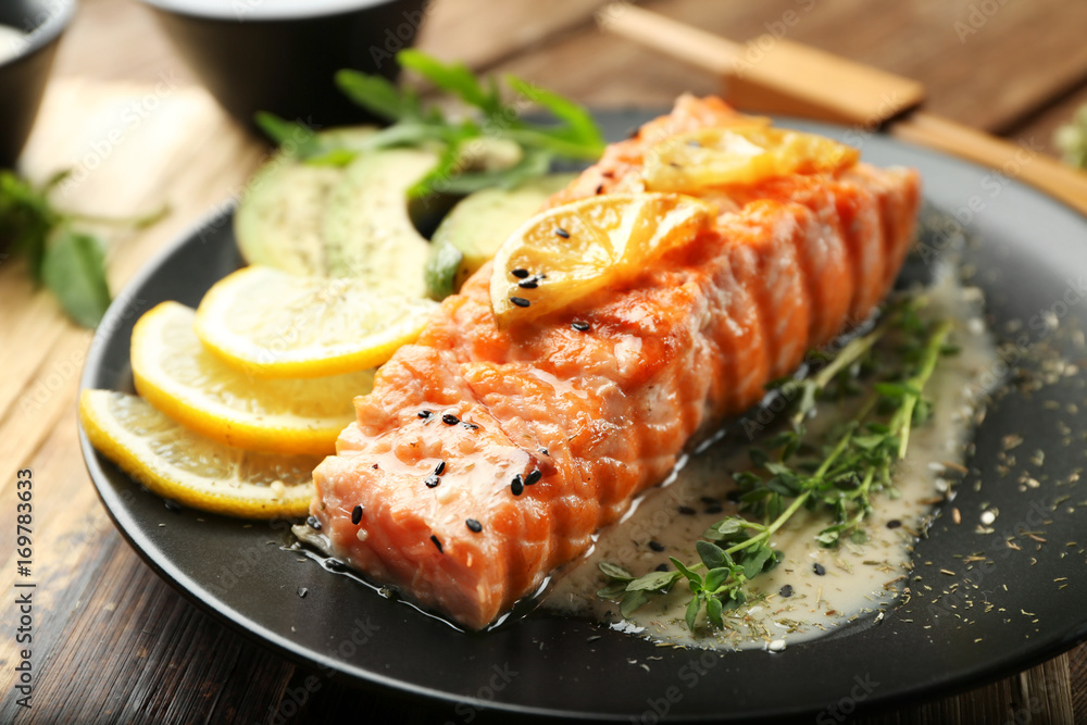 Fototapeta Plate with slice of delicious salmon and fish sauce on table