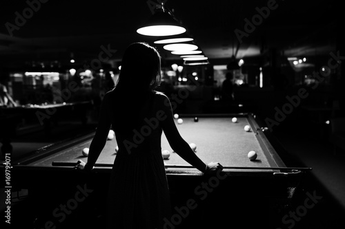 Fotografie, Obraz Portrait of an attractive young woman in dress playing pool