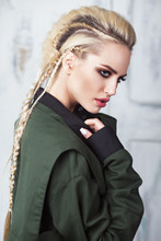 Creative Unusual Blond Girl In Designer Clothes And Braids On Her Head Posing In The Studio.