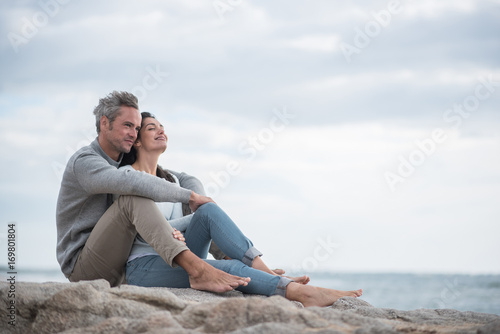 Fotografia  Portrait of a middle-aged couple sitting on the beach