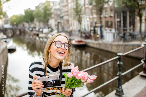 Photo  Portrait of a young woman tourist with photo camera and flowers standing on the