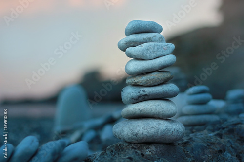 Fotografía  a pile of zen stones on the rocky beach during the sunset