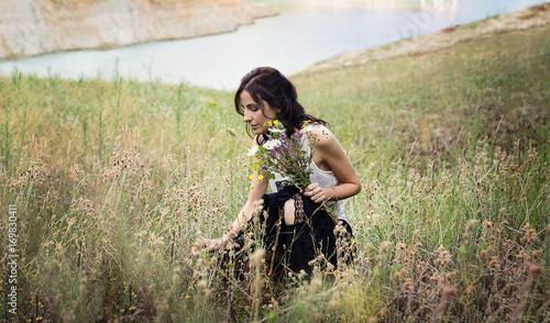 Fotografía  Giovane donna che raccoglie fiori selvatici in un prato di montagna