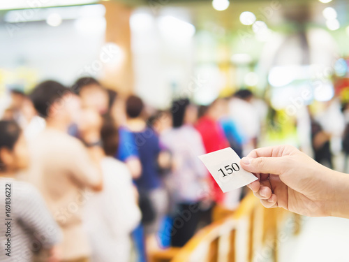 Fotografie, Obraz  Male hand holding queue card over long line waiting people