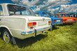 Three retro vehicles stand in a row of trunks