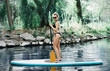 Young woman paddling on SUP board on the lake. Active summer vacations with paddle board.