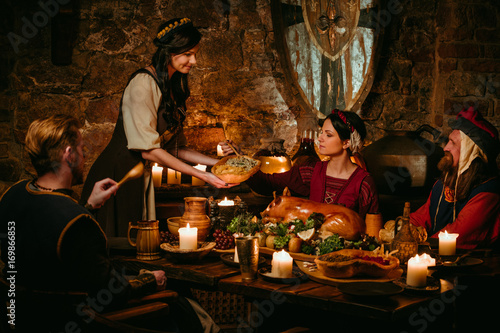 Fototapeta Medieval people eat and drink in castle tavern. obraz