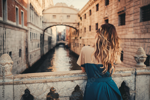 Fotografiet  Woman in front of Bridge of Sighs in Venice