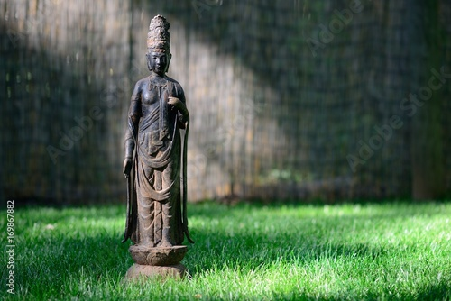 Photo Kuan Yin Bodhisattva statue resting in green grass