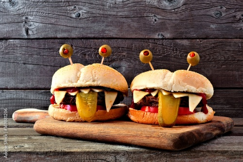 Fotografía  Halloween monster hamburgers on a paddle board against an old wood background