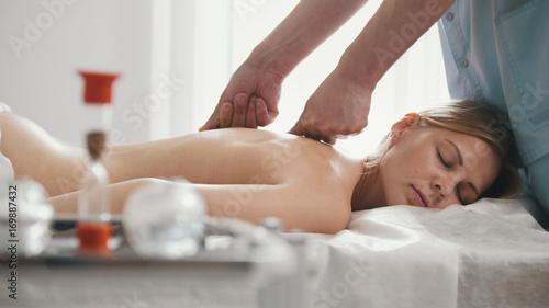 Obraz na płótnie Męski physiotherapist masowania kobiety plecy w medycznym biurze