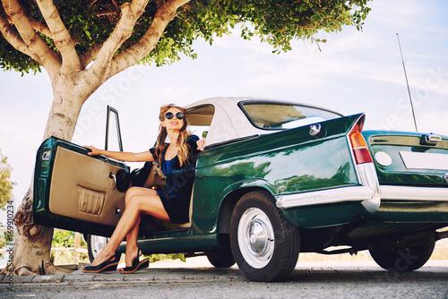 Beautiful happy woman sitting in a car. Retro styled