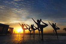 A Group Of Women Doing Yoga At...