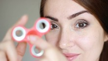 Young Woman Holding Rotating Spinner In Her Hand. Spiner Close-up. Closeup