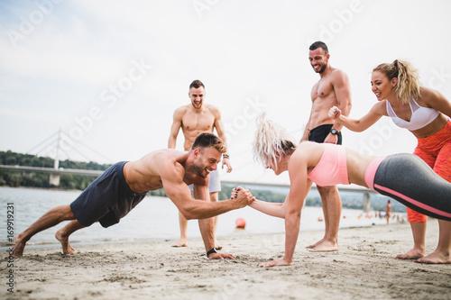 Plakat Grupują młodych atrakcyjnych ludzi ma zabawę na plaży i robi niektóre sprawności fizycznej trening.
