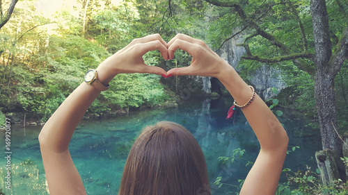 Fotografie, Obraz  Young woman holding heart-shape for the beautiful nature.
