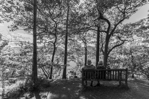 Fotografie, Obraz  Old couple on bench, Derwent Water lake, Keswcik, UK- monochrome
