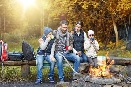 In de dag Kamperen happy family sitting on bench at camp fire