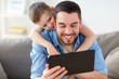 father and son with tablet pc playing at home
