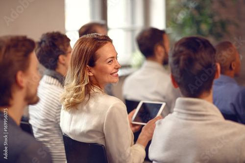 Fotografia Profile of smiling woman in audience on lecture on company meeting