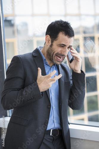 Uomo In Giacca E Camicia Parla Al Telefono Molto Arrabbiato Da