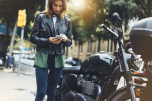 Girl In Leather Jacket Holding Smart Phone On Background Motorcycle In Sun Flare City, Hipster Using In Hands And Texting Mobile, Motorbike Street Lifestyle, Tourist Planing Route In Summer