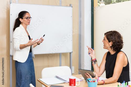 Dos mujeres, una en pie y otra sentada, dialogan con una pizarra blanca de fondo Canvas-taulu