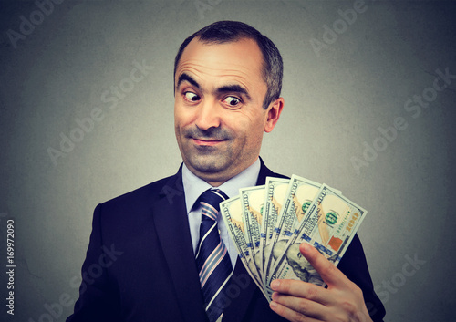 Obraz na plátně Funny sly business man holding looking at money dollar banknotes