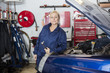 Mechanic Holding Socket Wrench By Car In Garage