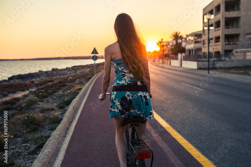 From behind: young woman riding a bike