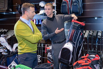 senior man in golf store talking to shop assistant